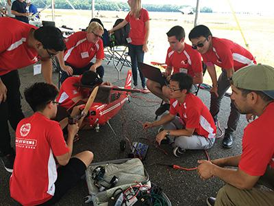 Photo of team doing pre-flight check for model airplane
