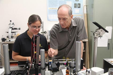 Photo of Raymond Kostuk and student testing a bench-top imaging instrument.