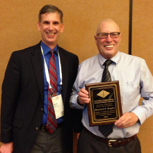 Douglas Morrice (left), co-chair of the INFORMS selection committee, presents the lifetime achievement award to ECE Professor Emeritus Bernard Zeigler for his pioneering work in simulation. (INFORMS/Susan Hunter)