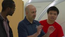Associate professor Ali Bilgin (center) speaks with two of his grad students in front of an MRI machine.