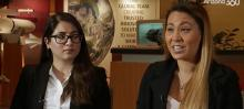 Screen capture of a video. Two women in dark suit jackets are sitting in a TV studio. The one on the right is mid-word.