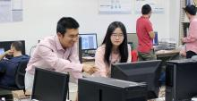 Ming Li and Yanjun Pan, facing the camera, look at a computer monitor in the foreground. Li is pointing at the screen.