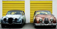 Two broken down classic Jaguar cars sitting before yellow garage doors.
