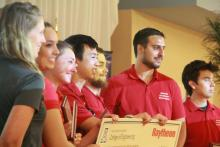 ECE students Jeremy Gin, Mark Roche and Jaime Lara Martinez accept the Raytheon Sensintel Best Overall Design Award with their teammates at the 13th annual Engineering Design Day.