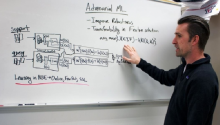 "Gregory Ditzler points at a whiteboard covered in a series of math equations. The top says ""Adversarial ML."""