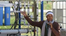Diné College student and Indige-FEWSS participant Larry Moore demonstrates use of the solar-powered water filtration system to community members on Navajo Nation