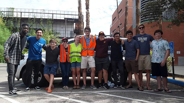 University of Arizona REU students, some in yellow and orange safety vests, stand together in front of the UA CAT vehicle