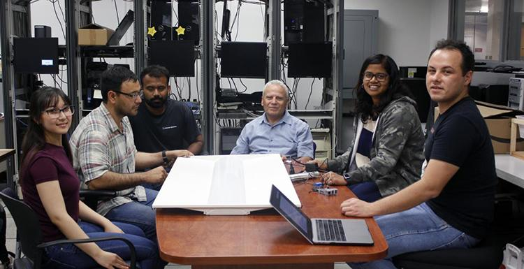 Students and faculty sit around a table with computer hardware in the background behind them.