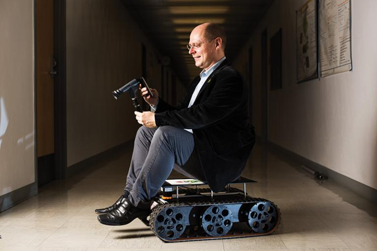 Wolfgang Fink with two of his inventions: a smart ophthalmoscope cell phone application, and a planetary rover