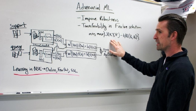 """Gregory Ditzler points at a whiteboard covered in a series of math equations. The top says """"Adversarial ML."""""""