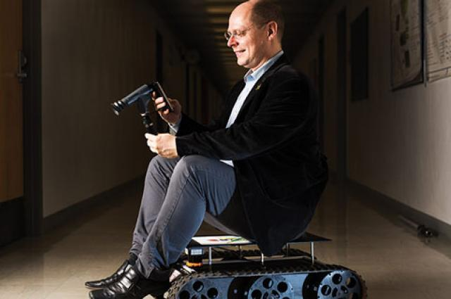Wolfgang Fink examines a smartphone-based ophthalmoscope while sitting on a planetary rover; both encapsulate his artificial vision research.
