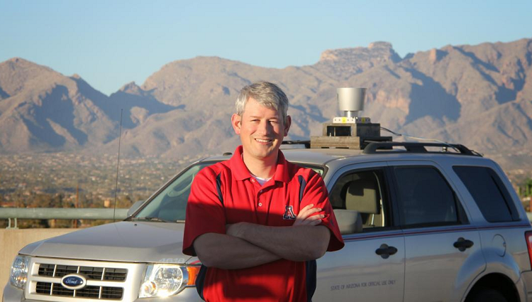 Jonathan Sprinkle stands in front of the CAT Vehicle -- an SUV with a cylindrical device on top. The Catalina Mountains are in the background.