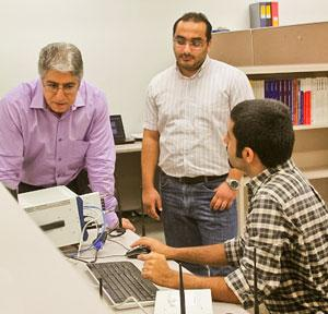 From left, ECE Professor Marwan Krunz and doctoral students Wessam Afifi and Hanif Rahbari (seated) analyze wireless transmission signals in the lab.