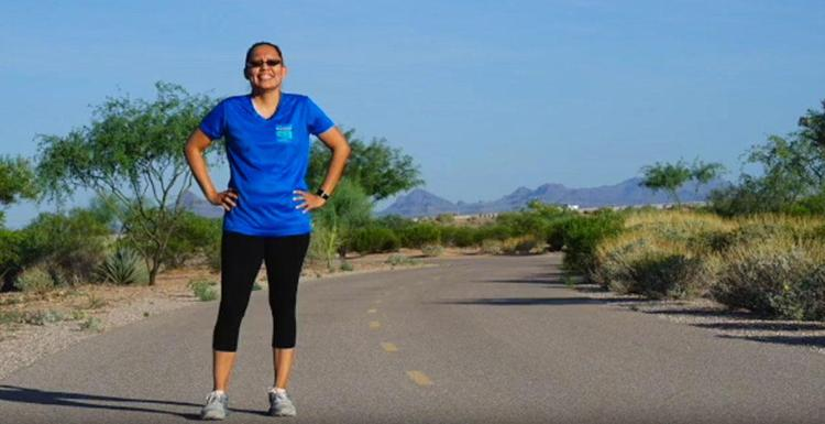 A woman with her hands on her hips, standing on a jogging path