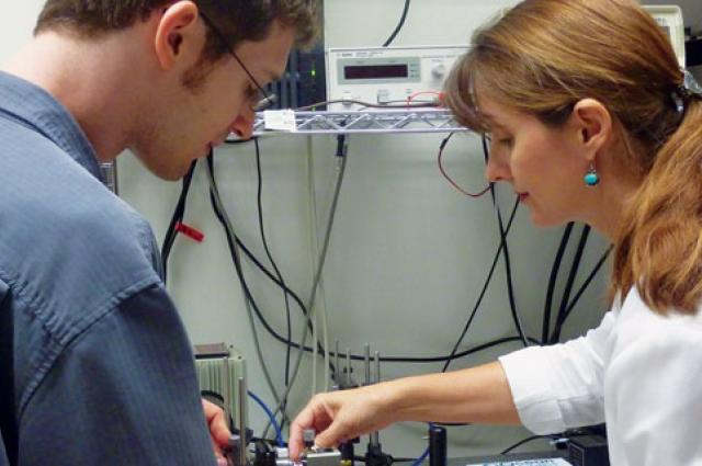 Kelly Simmons-Potter, right, and ECE grad student Brian Fox work on a joint research project investigating space-hardened fiber optics.