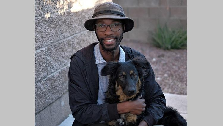 Ahanonu poses with a dog