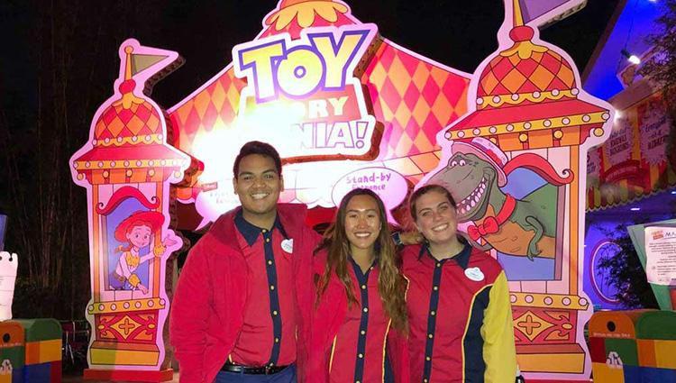 Three smiling people in Disney uniforms stand in front of the Toy Story Mania! attraction.