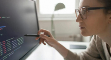 A woman studies computer code