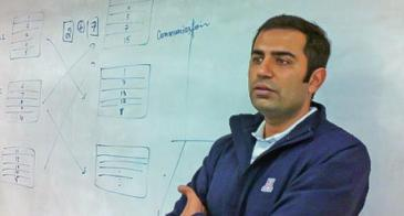 Ravi Tandon stands in front of a whiteboard in a blue UA jacket